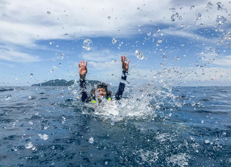 De vrouw die van Azië in overzees en plonswater aan camera zwemmen Jongen en de meisjes die bij het surfen van bureau de zitten e stock afbeeldingen