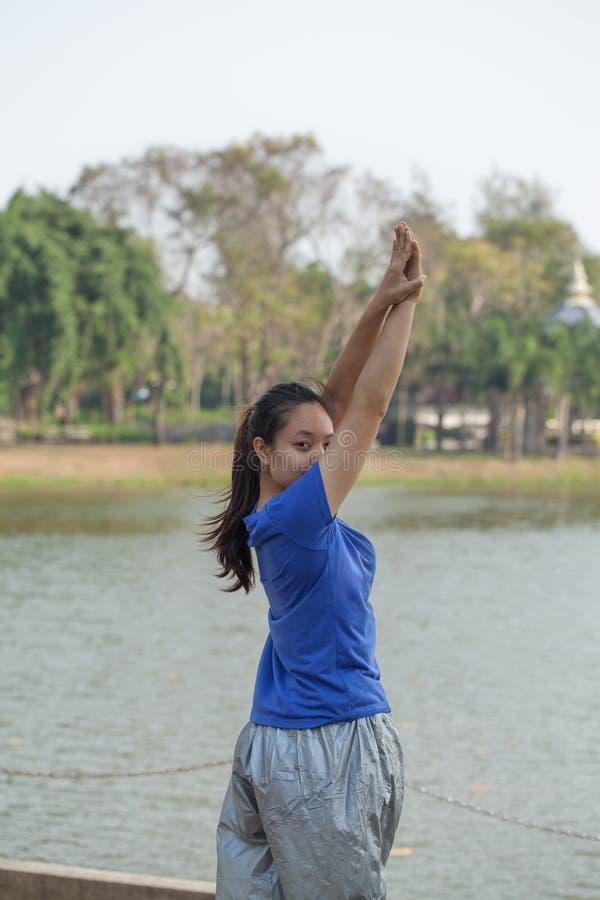 De vrouw die van Azië vóór haar ochtendtraining opwarmen in de Tuin royalty-vrije stock afbeelding