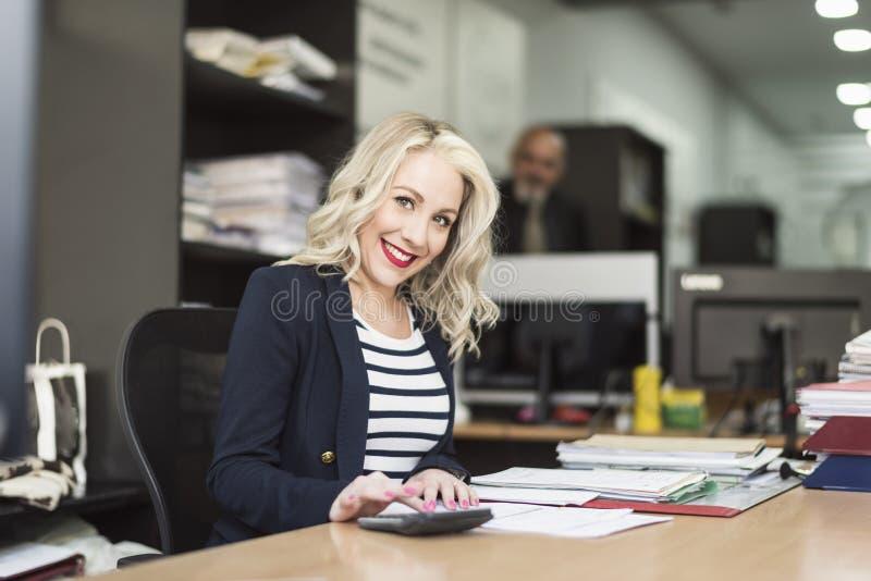 De vrouw die van blondejaren '30 op kantoor en het glimlachen werkt stock foto