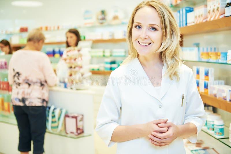 De vrouw die van de apothekerchemicus in apotheekdrogisterij werken stock fotografie