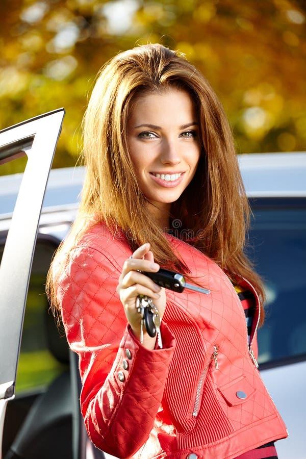 De vrouw die van de autobestuurder nieuwe autosleutels en auto tonen. royalty-vrije stock foto's
