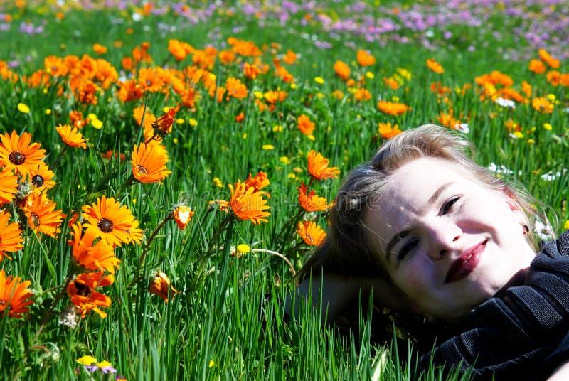 De vrouw die van de blonde in een gebied van bloemen ligt stock afbeeldingen