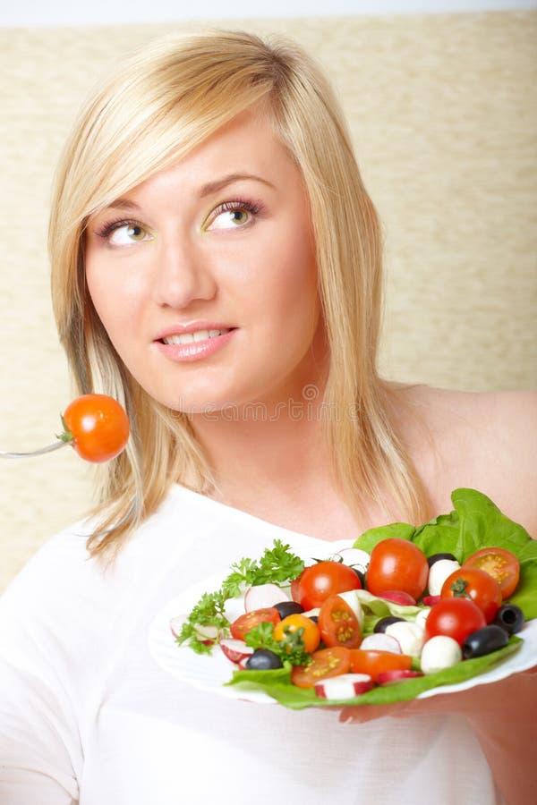 De vrouw die van de blonde gezond voedsel, Griekse salade eet stock afbeeldingen