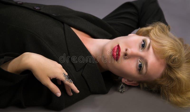 De vrouw die van de blonde op de vloer ligt stock fotografie