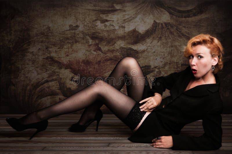 De vrouw die van de blonde op de vloer ligt royalty-vrije stock foto's