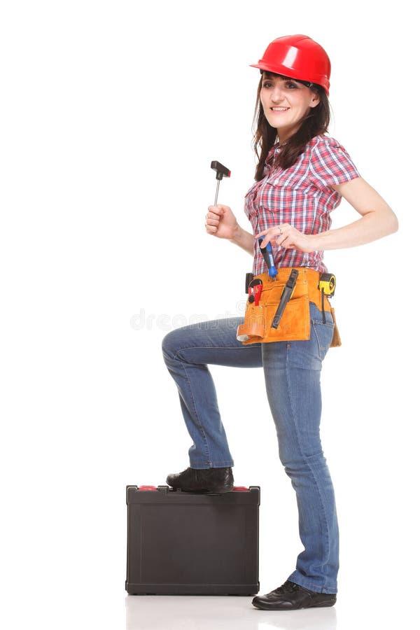 De vrouw die van de bouwer zich met hulpmiddelen bevindt stock afbeeldingen