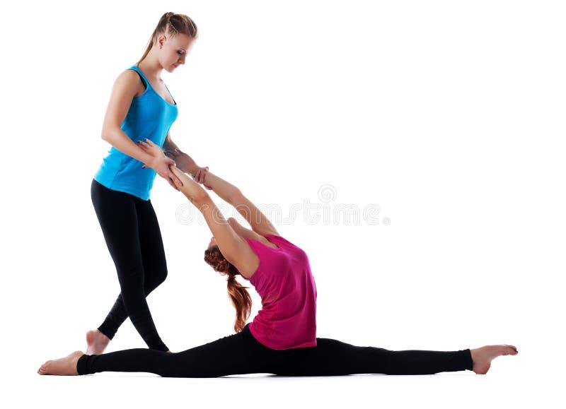 De vrouw die van de de instructeurshulp van de geschiktheid yogaasana doet royalty-vrije stock fotografie