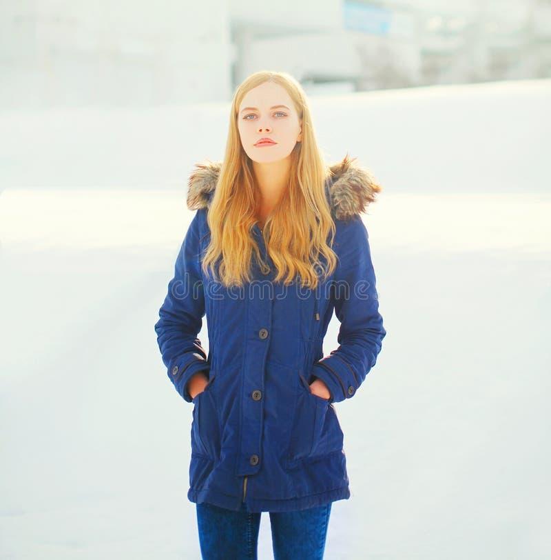 De vrouw die van de de wintermanier jasje over sneeuw dragen royalty-vrije stock foto