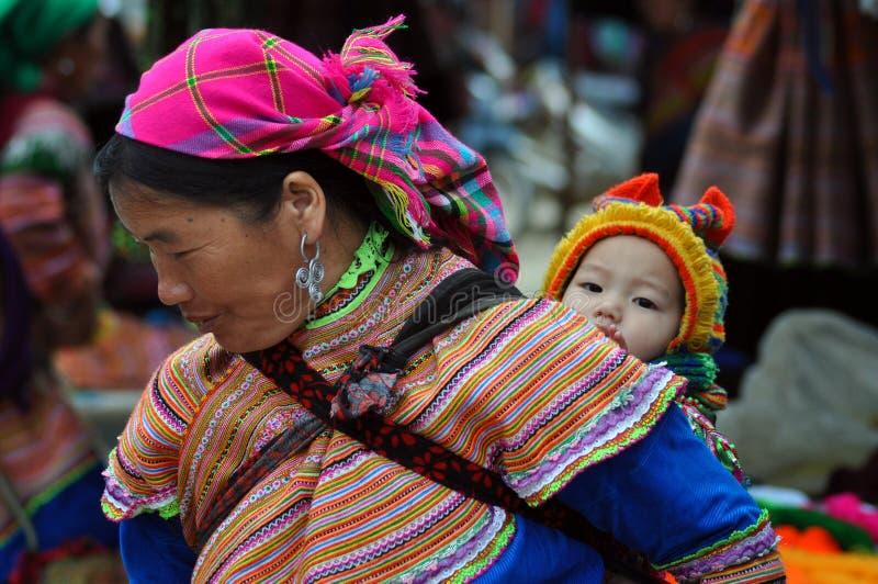 De vrouw die van de Hmongstam haar kind, Bac Ha, Vietnam vervoeren stock foto's