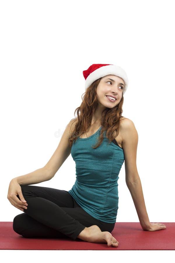 De vrouw die van de Kerstmisyoga ruggegraatsdraai doet stock afbeelding