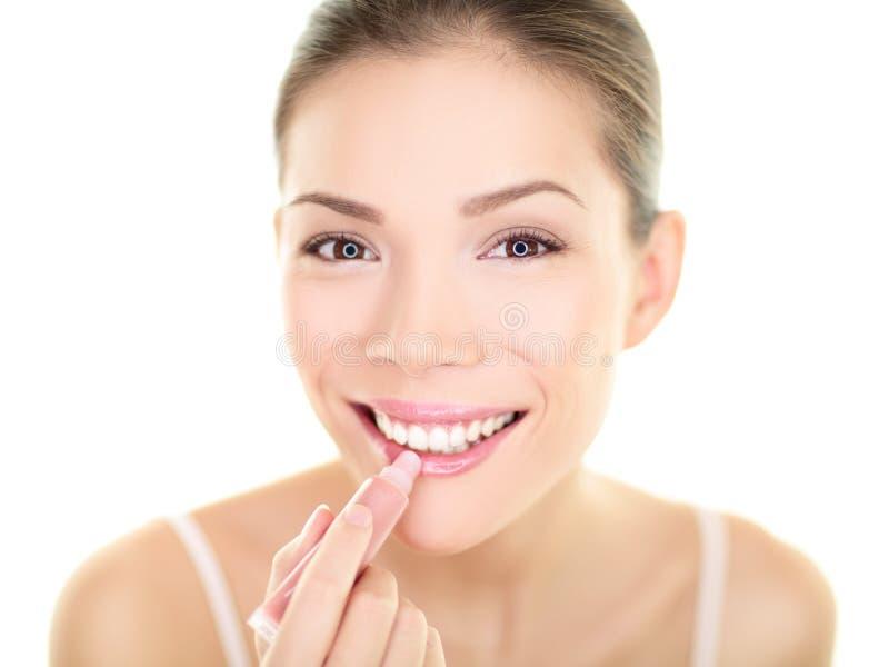 De vrouw die van de lippenstiftmake-up de schoonheid van de lippenpommadezorg zetten stock fotografie