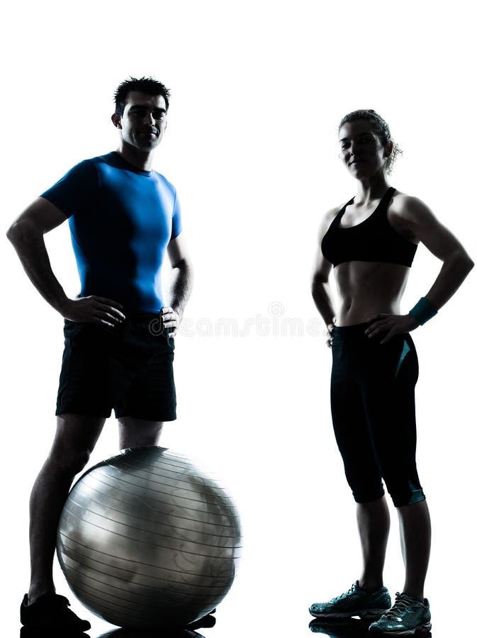 De vrouw die van de man de bal van de traininggeschiktheid uitoefent stock afbeeldingen