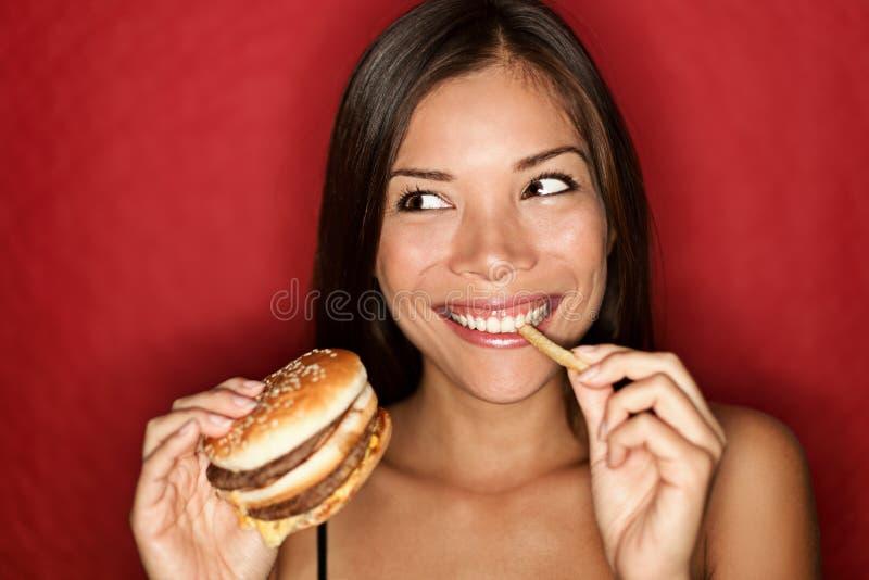 De vrouw die van de ongezonde kost hamburger eet royalty-vrije stock foto