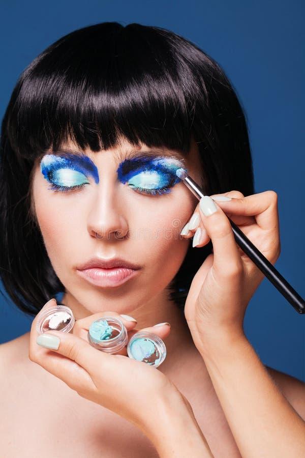 De vrouw die van de oogmake-up blauw oogschaduwpoeder toepassen stock afbeeldingen