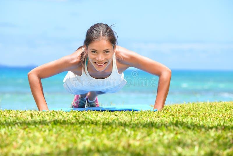 De vrouw die van de opdrukoefeningengeschiktheid opdrukoefeningen buiten doen stock foto