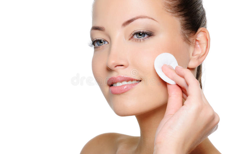 De vrouw die van de schoonheid haar gezicht met katoenen zwabber schoonmaakt royalty-vrije stock afbeelding
