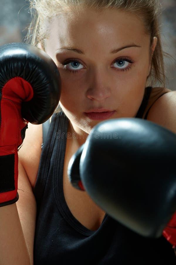 De vrouw die van de vechter bokshandschoenen draagt stock afbeelding