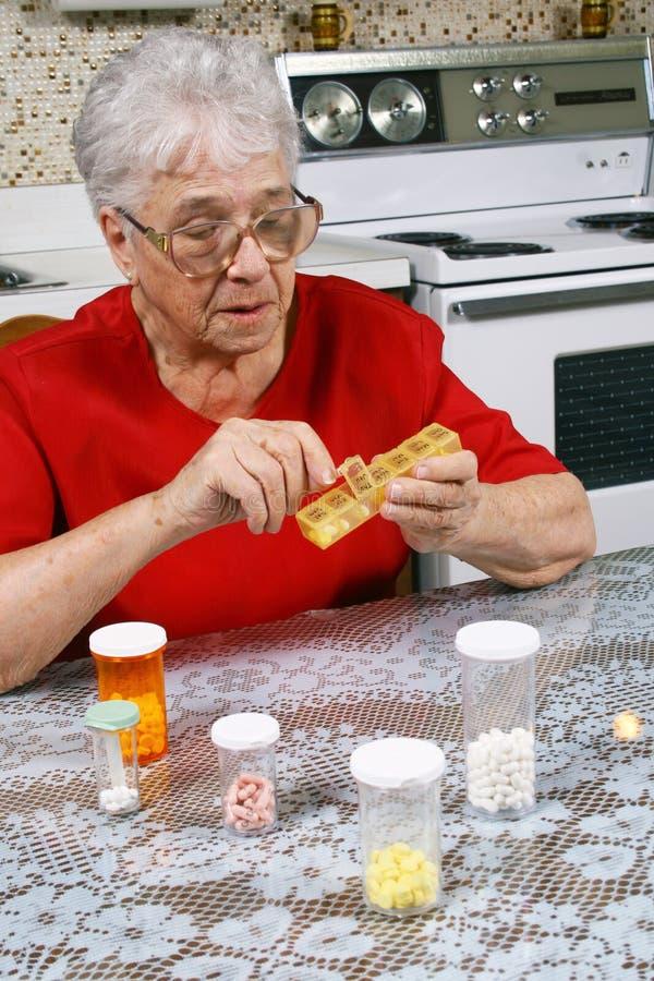 De vrouw die van Ederly pillen neemt stock afbeelding