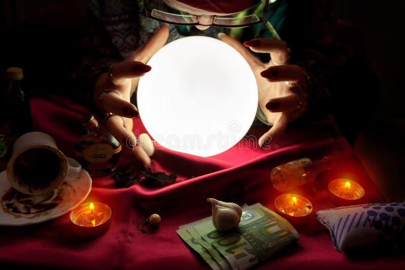 De vrouw die van de fortuinteller kristallen bol met haar handenarou bekijken stock foto