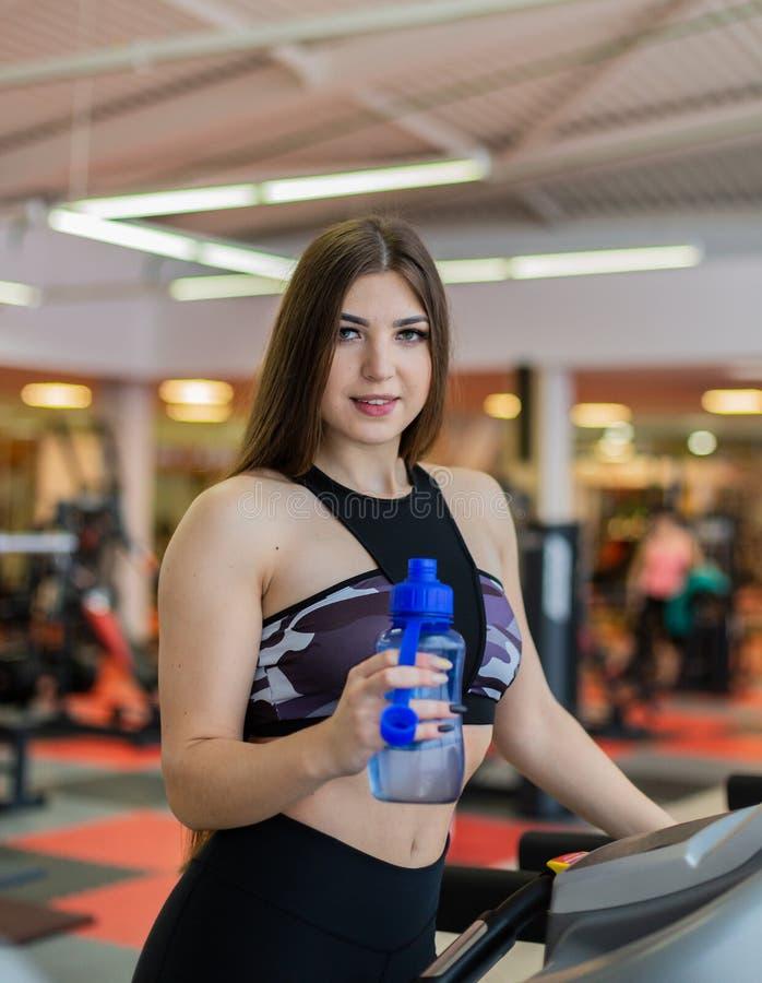 De vrouw die van de gymnastiek drinkwater uitwerkt dat gelukkige status glimlacht door de machines van de moonwalkergeschiktheid  stock afbeeldingen