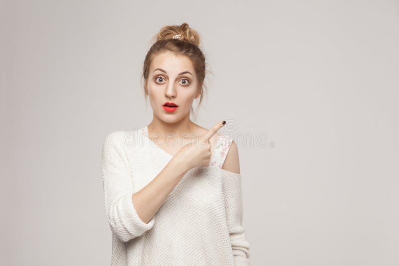 De vrouw die van het verbazingblonde vinger richten op exemplaarruimte stock foto's