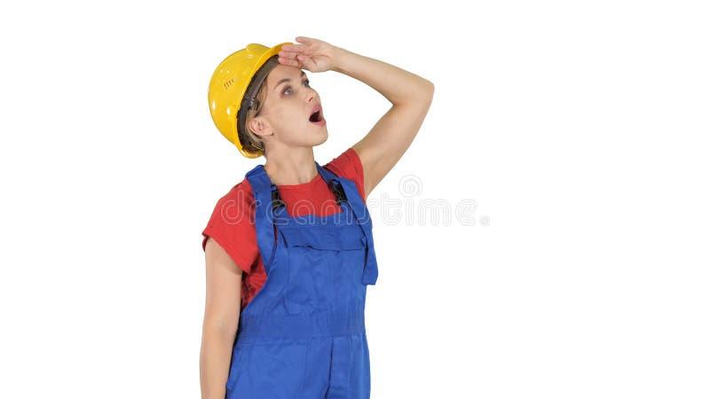 De vrouw die van de ingenieursbouwvakker kijkt die omhoog op witte achtergrond wordt verbaasd royalty-vrije stock afbeelding