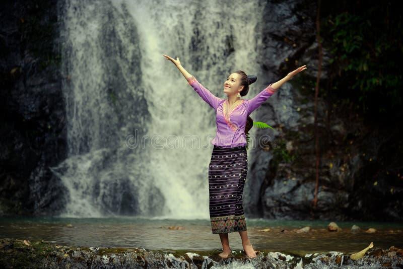 De Vrouw die van Laos de traditionele kleding van Laos dragen geniet van met aardhaven stock afbeelding