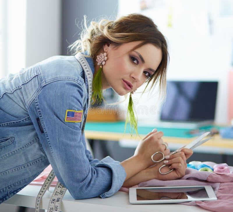 De vrouw die van de manierontwerper aan haar ontwerpen in de studio werken stock foto's