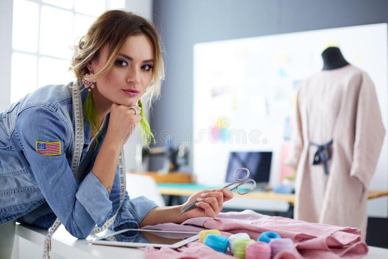 De vrouw die van de manierontwerper met ipad aan haar ontwerpen in de studio werken stock afbeelding
