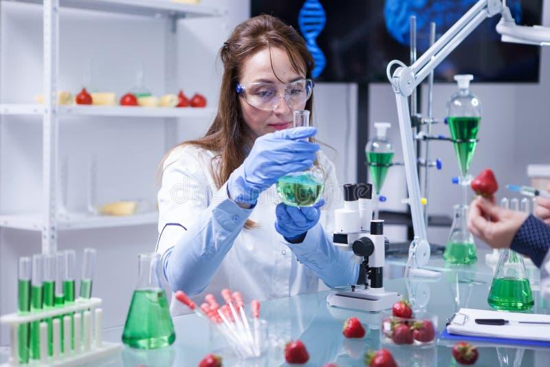 De vrouw die van de middenleeftijdswetenschapper beschermingsglazen in een onderzoeklaboratorium dragen stock afbeelding