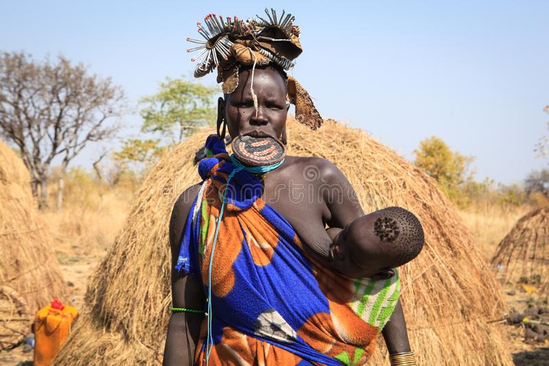 De vrouw die van de Mursistam haar jong geitje de borst geven royalty-vrije stock afbeelding