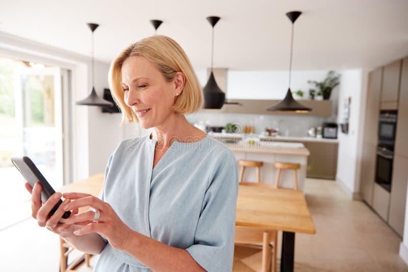 De vrouw die van de natuur app op mobiele telefoon gebruikt om de centrale verwarmingstemperatuur in huis te controleren royalty-vrije stock foto
