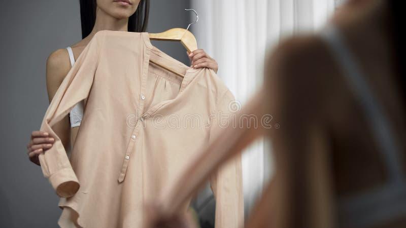 De vrouw die van Nice blouse voor spiegel in garderobe proberen, die voor datum voorbereidingen treffen royalty-vrije stock foto