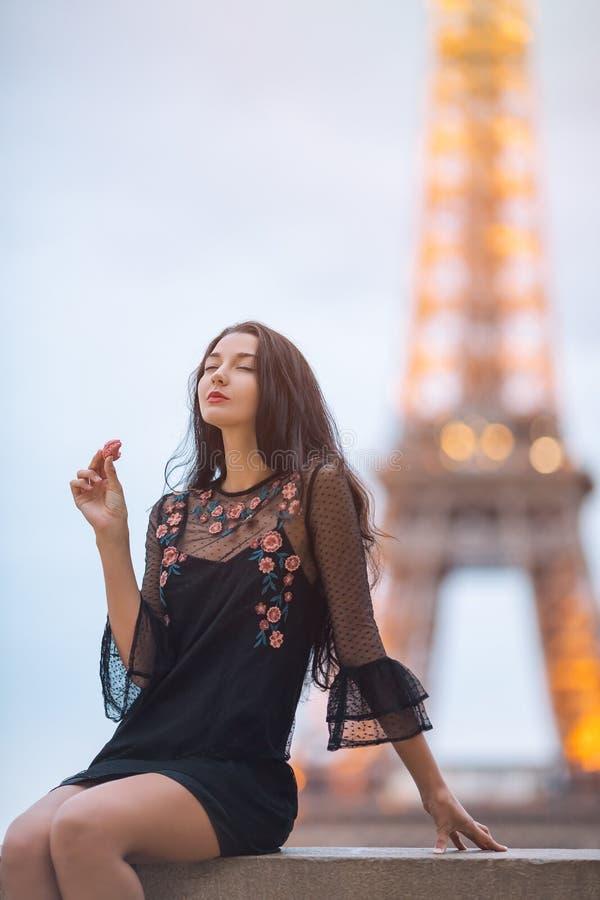De vrouw die van Parijs etend het Franse gebakje macaron in Parijs tegen de toren van Eiffel glimlachen stock foto