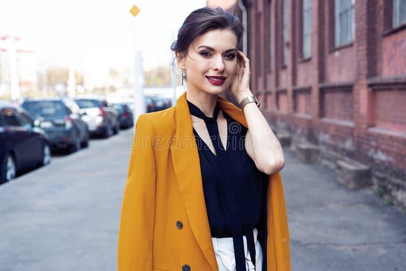 De vrouw die van de portretmanier op straat lopen Zij draagt geel jasje, glimlachend aan kant royalty-vrije stock fotografie