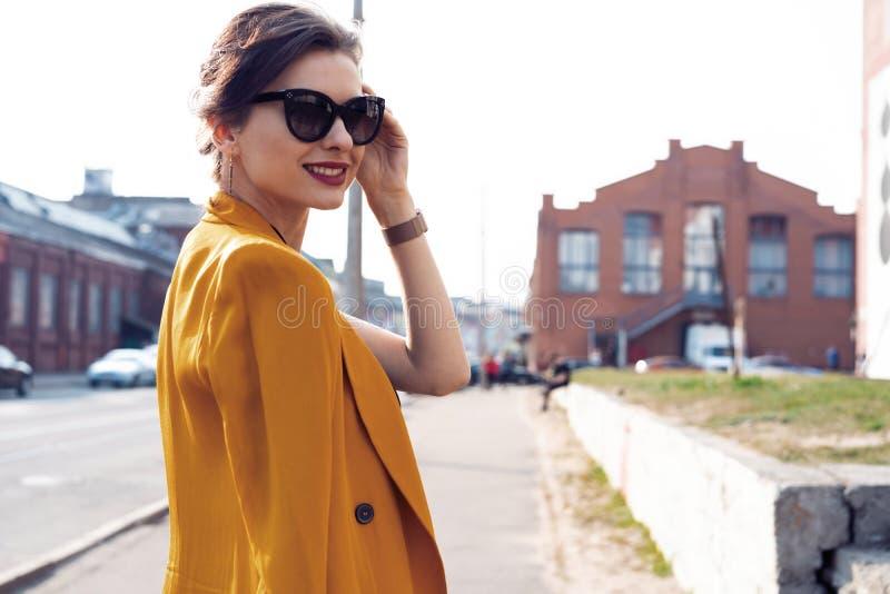 De vrouw die van de portretmanier in zonnebril op straat lopen Zij draagt geel jasje, glimlachend aan kant stock foto's