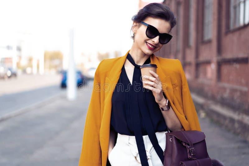 De vrouw die van de portretmanier in zonnebril op straat lopen Zij draagt geel jasje, glimlachend aan kant stock foto