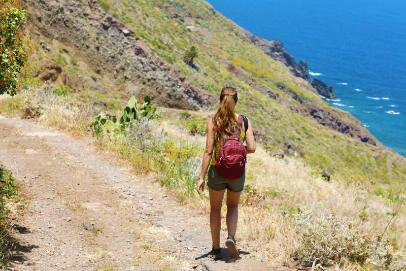 De vrouw die van de reizigerswandelaar langs de weg op de bergen van Tenerife lopen Natuurlijk het avonturenconcept van de toeris stock afbeelding