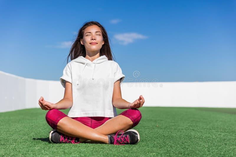 De vrouw die van de yogageschiktheid de zomermeditatie doen openlucht stock fotografie