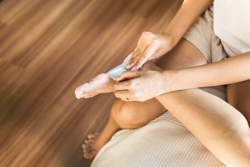 De vrouw die wit flard gebruiken voor verlicht pijn en ontspant te voet, Verwondingsvoeten royalty-vrije stock fotografie