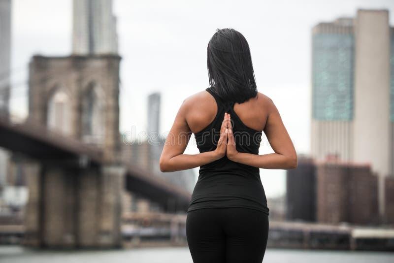 De vrouw die yoga doen stelt met wapens op de rug in de Stadspark van New York Het concept van yogaklassen stock afbeelding