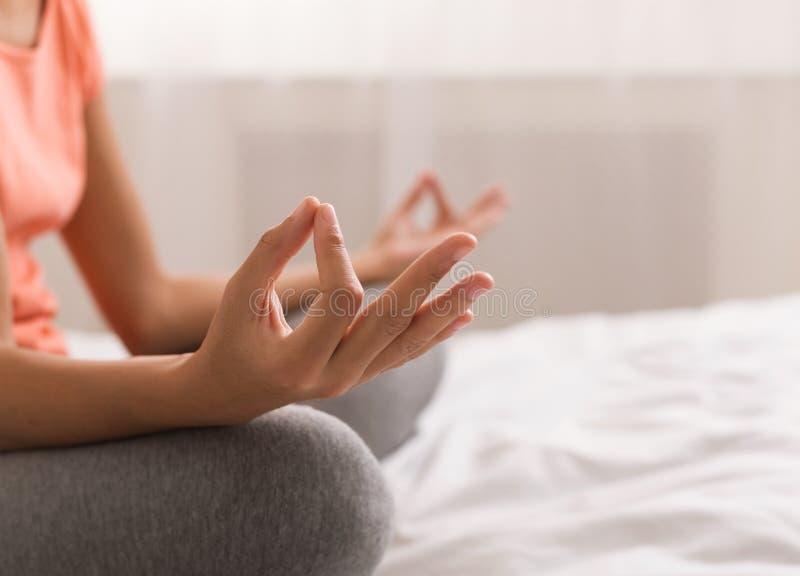 De vrouw die yogalotusbloem doen stelt omhoog op bed na kielzog stock afbeeldingen
