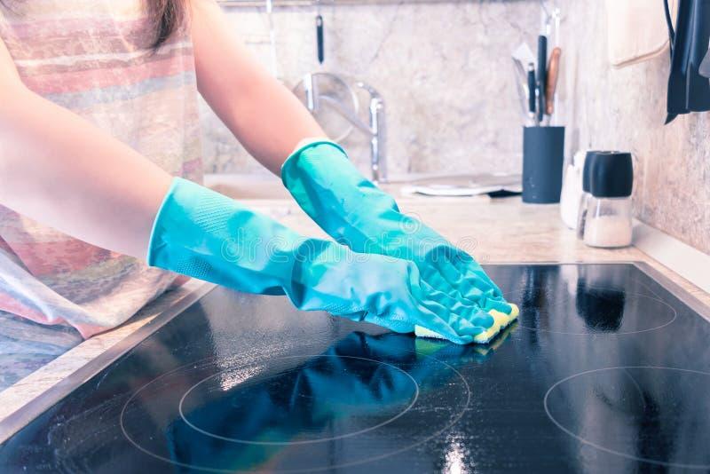 De vrouw dient een handschoen in schoonmaakt een zwart kooktoestelpaneel stock afbeelding