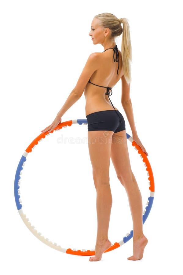 De vrouw doet gymnastiekoefeningen met hoepel stock foto