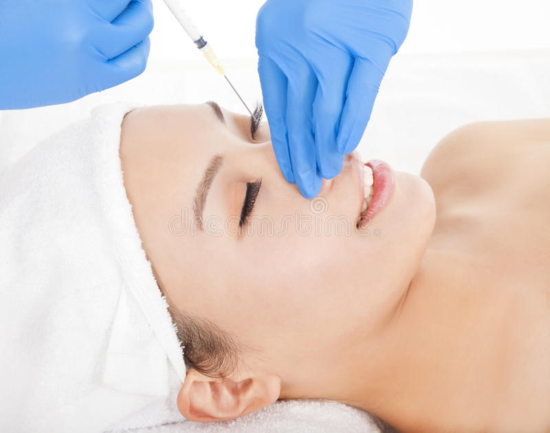 De vrouw doet kosmetische chirurgieinjecties stock foto