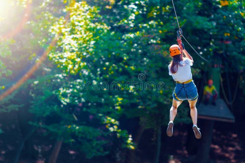 De vrouw draagt beschermende helm geniet van actieve vrije tijd in kabelpark royalty-vrije stock afbeelding