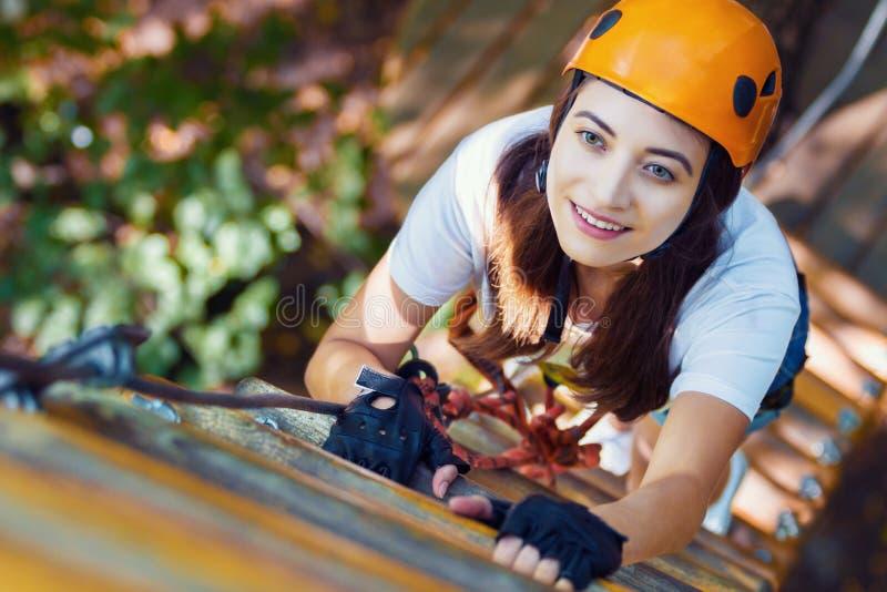 De vrouw draagt beschermende helm geniet van actieve vrije tijd in kabelpark royalty-vrije stock foto's
