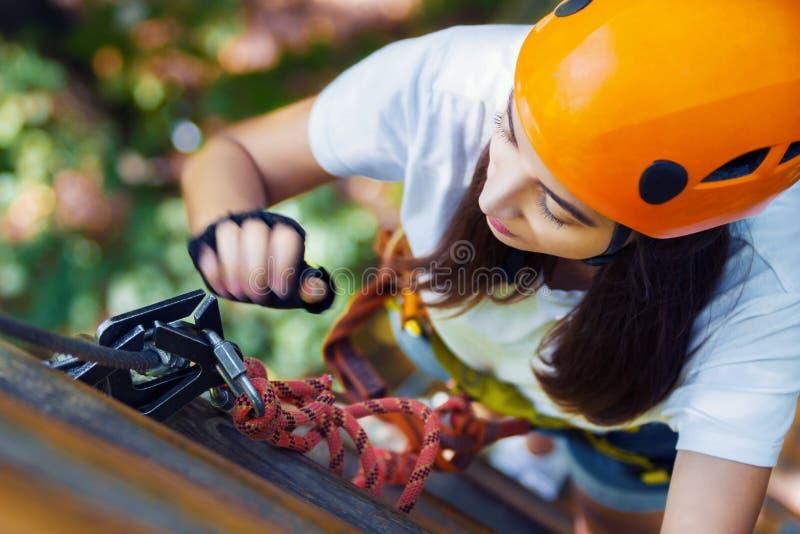 De vrouw draagt beschermende helm geniet van actieve vrije tijd in kabelpark royalty-vrije stock foto