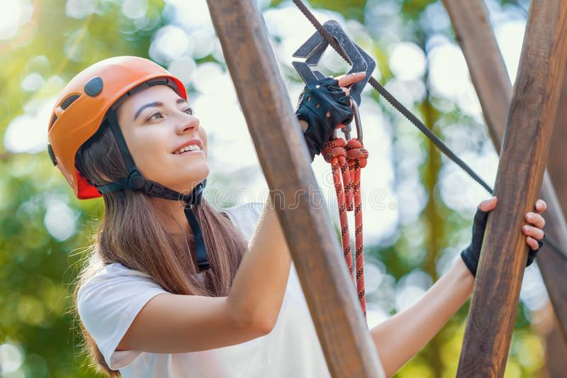 De vrouw draagt beschermende helm geniet van actieve vrije tijd in kabelpark stock afbeeldingen