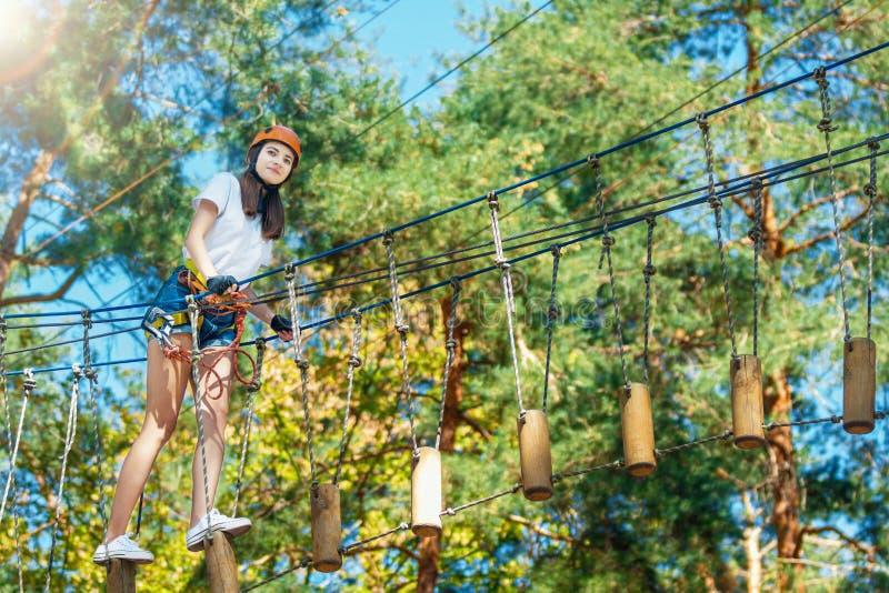 De vrouw draagt beschermende helm geniet van actieve vrije tijd in kabelpark stock fotografie